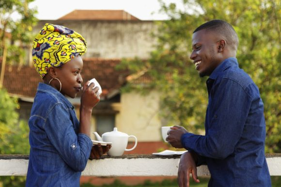 People smiling at each other while having a cuppa tea